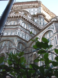 The dome and apse of Florence Cathedral seen through the foliage around the Bottegha di Donatello