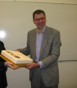 Mark Blackburn receiving a cake bearing the cover of his new volume of collected essays