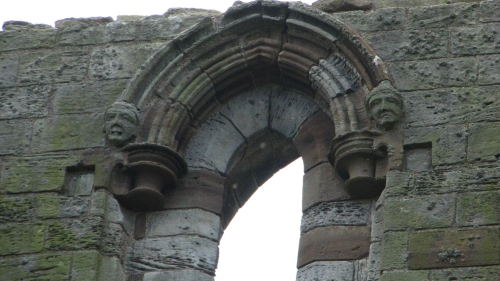 Heads as ornament of an arched window at Whitby Abbey