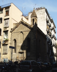 A fourteenth-century church slowly mouldering between more modern buildings on a Naples street