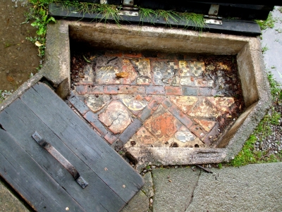 Medieval floor tiles in partially-weatherproof display housing, Glastonbury Abbey