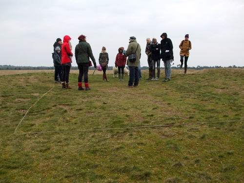 Visitors standing above the location of the burial chamber of Mound 1 at Sutton Hoo