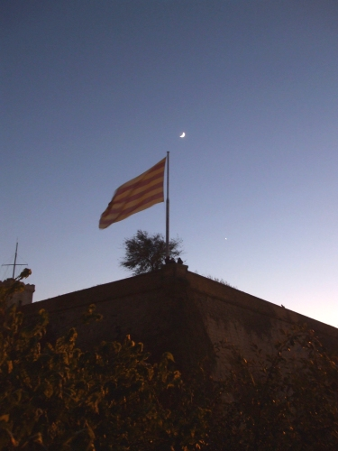 Flag at a corner of the Castell de Montjuïc, Barcelona, with the evening moon above