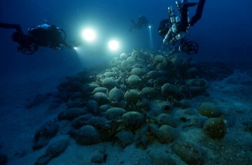 Divers over an ancient shipwreck off the coast of Sicily