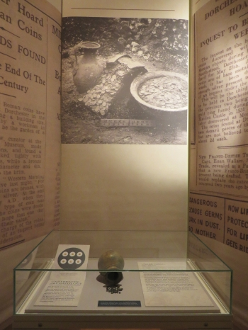 Coins from the Messina Hoard and a replica of one of the vessels from the Dorchester Hoard against a backdrop of photographs from that hoard's discovery in 1936, in the exhibition Buried Treasures: Uncovering Hoards, at the Barber Institute of Fine Arts, University of Birmingham